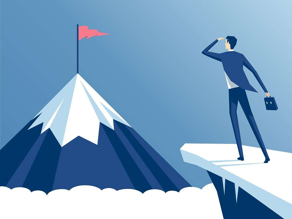 A man (investor) standing on a cliff, and staring at his goal - a mountain peak (his goal)